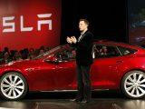 Elon Musk a lado de un Tesla rojo